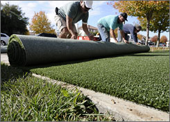 Workers roll up synthetic grass as they prepare to install it in the backyard of a Chino Hills home.
