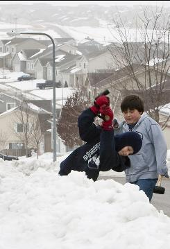 Eric Aragon, 11, right, and his brother Isaac, 9, attempt to break up ice deposits in front of their in Omaha, home on Tuesday. Another winter storm is forecast to hit the Midwest before Christmas.