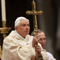 Pope Benedict XVI holds a cross as he leads the Christmas Mass in Saint Peter's Basilica at the Vatican on Thursday.