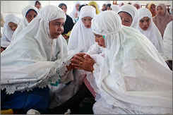 Acehnese women comfort each other while taking part in a mass prayer for the victims of the Indian Ocean tsunami of 2004 in the Mosque Rahmatullah, Friday, in Banda Aceh, Indonesia.