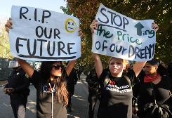 Student protesters hold banners outside a police line during a protest against an increase in student fees at the UCLA campus Nov. 19.