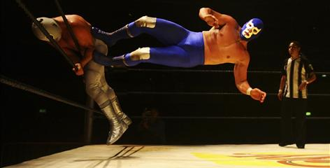 Mexican luchador Blue Demon Jr. dropkicks Hijo del Santo during a July 5, 2008 bout in London. Luchadors have occasionally competed on pro wrestling circuits in the United States, Europe and Japan.
