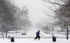 Two people jog on the snowy sidewalk of Constitution Avenue in Washington, D.C., Dec. 19.