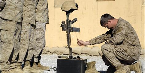 A U.S. special operations member pays final respects on Nov. 9 for a comrade killed two days earlier in Afghanistan's Farah province.