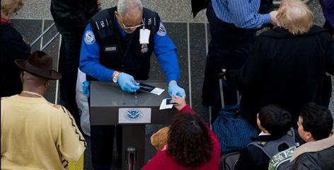 A Transportation Security Administration official checks the identification of passengers prior to entering a security checkpoint at Ronald Reagan Washington National Airport in Arlington, Va. Security measures have been increased after an alleged terror plot.
