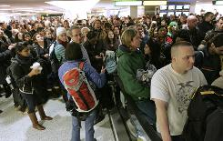 Crowds of people wait to take the escalator to the departure level after a security scare shut down Terminal C at Newark Liberty International Airport in Newark, N.J., on Sunday.