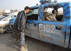 An Iraqi policeman inspects a police vehicle on Monday damaged in a roadside bomb attack in Kirkuk, 180 miles north of Baghdad.