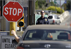 A U.S. Customs and Border Protection officer looks toward a car coming toward him on Saturday crossing between the U.S. and Canada in Blaine, Wash.