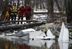 Investigators look over the wreckage of a small cargo jet that crashed into the banks of the DesPlaines River in a forest preserve near Wheeling, Ill., on Tuesday. The plane went down as it approached Chicago Executive Airport.