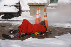 A homeless man sleeps next to a manhole in Washington, D.C., after a snowstorm blanketed much of the East Coast last month.
