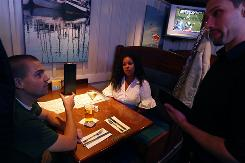 Aaron and Kendra Johnson order from server Chris Pitman at Newport Bay Restaurant in Seattle, which accomodates both of their food allergies.