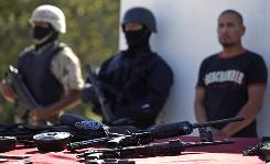 Sebastian Gonzalez, right, a suspect in a police shooting, is put on display during a news conference along with seized weapons in Tijuana, Mexico, on Oct. 28.