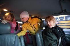 Angela Allyn talks with 9-year-old daughter Tess and 12-year-old son Alec as they climb out of their minivan, arriving at school in Evanston, Ill. The family is saving $20,000 by sending the kids to public school instead of private.
