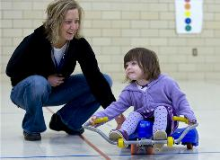 Physical therapist Stacey Hess-Norskog encourages Julieanna Metcalf to move the scooter with her arms at preschool. Julieanna's mom takes her to therapy to help her make up for developmental delays caused by meningitis.