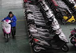 A worker moves an electric bike through a factory in Hefei, in central China. China is pushing its exports as the global economy recovers.