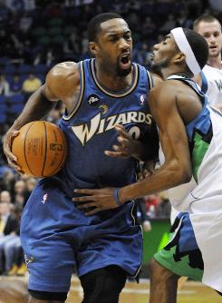 The Washington Wizards' Gilbert Arenas is defended by the Minnesota Timberwolves' Corey Brewer on Dec. 26 in St. Paul. Adidas is reviewing its relationship with Arenas after he was suspended indefinitely from the NBA.
