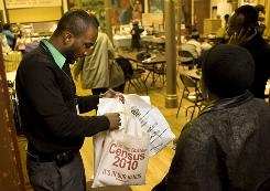 Census worker Samuel Darguin, left, distributes 2010 Census information at a Haitian Independence Day celebration in Brooklyn, N.Y.