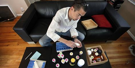 Scott Bowles, 44, starts off each week arranging his medicines in his calendar pack. Keeping 26 bottles of medicine, he takes over a dozen different meds at any one time.