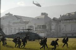 A U.S. Navy helicopter takes off in front of the National Palace after members of the U.S. Army 82nd Airborne land in Port-au-Prince onTuesday, Jan. 19.