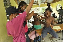 In Leogane, Haiti, a young quake victim cries in pain as a wound is cleared in a Cuban-run field hospital. Aid to the city hit hard by the quake has been slow.
