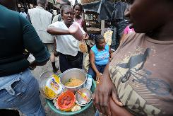 A Haitian market vendor makes food for clients in Jacmel on Tuesday.