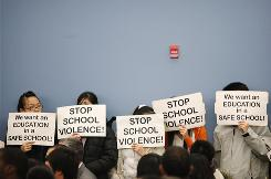 Holding signs in front of their faces, Asian students stand during a school board meeting to express concerns about assaults at a Philadelphia high school Dec. 9.