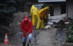 George Wiktor helps divert water from a backyard in the La Canada Flintridge area of Los Angeles.