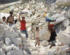 Residents walk amid the ruins of a Catholic church in Petit Goave, Haiti, a town about 30 miles west of Port-au-Prince.