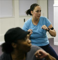 "Melissa Dilling, 28, right, follows the lead of cardio kickboxing class instructor Rachel Tyson. After losing 25 pounds, ""I have more self-confidence,"" Dilling says."