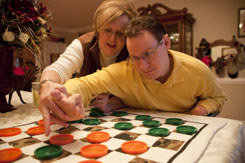 Beth Edmundson helps her son Eric move checker pieces during a game in their New Bern, N.C., home Jan. 22. Eric suffered traumatic brain injuries in Iraq that left him unable to care for himself.