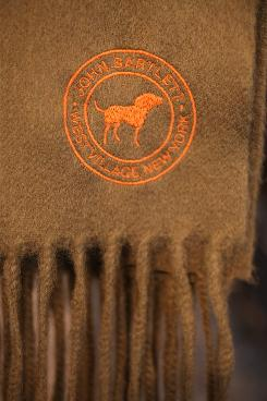 Bartlett's clothing logo on a men's scarf shows his three legged dog, Tiny Tim. It's also on the store front, shirt sleeve and other items in the boutique.