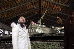Visitors examine an obsolete Chinese-made tank displayed at the military museum in Beijing, China. China criticized the U.S. ahead of the expected announcement of new arms sales to Taiwan and will likely suspend U.S. military exchanges in response.