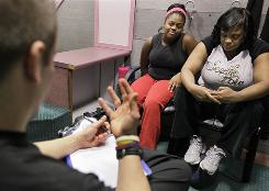 Paris Woods, left, and her mother Dinah Woods listen to personal trainer Scott Mathews' instructions as they take part in their final session of a 20-month obesity prevention study at Rush University Medical Center in Chicago.