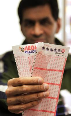 Biren Shah displays the Mega Millions and Powerball slips Friday at his newstand in Chicago.