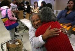 Lydia Anaya embraces Sofia Ordonez after Anaya received a food basket from the Open Arms Catholic Community Dec. 19 at Our Lady of Mt. Carmel Church in El Paso.