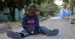 A boy who was found with a U.S. church group plays with stones at an orphanage in Port-au-Prince.