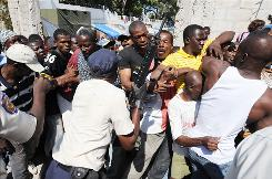 Haitian police push back people waiting in a line Tuesday during water distribution in Port-au-Prince.