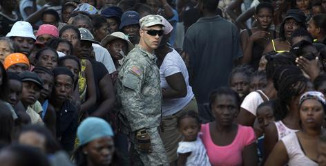 An 82nd Airborne Division soldier stands among a crowd of about 2,000 people to help maintain order as they line up for water distribution at a camp set up on a golf course in Port-au-Prince on Wednesday.