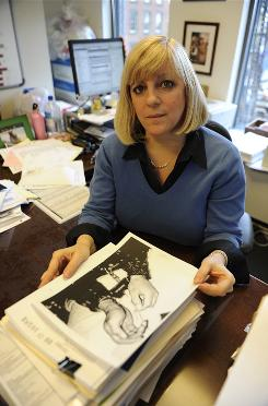 Tamara Steckler, Legal Aid attorney, holds a photo of one of her clients wearing restraints.