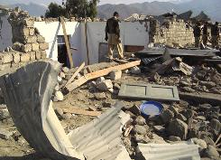 Pakistani officials inspect the site of bombing in Lower Dir, Pakistan on Wednesday.