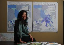"Quyen Vouong sits in front of Census maps of ""hard to count"" areas at her office in San Jose."