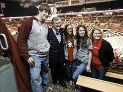 Ohio State president E. Gordon Gee, second left, poses with a group of students before an OSU women's basketball game against Minnesota Jan 28. Taking on tenure will be the third big academic undertaking for Gee.