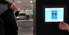 A security officer demonstrates the body scanner at Manchester Airport in England on Jan. 7. Travelers worldwide could see longer security lines and more congested terminals because of body scanners.