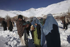 Afghans, carrying a few possessions, walk toward a restaurant after being evacuated following heavy snow that caused an avalanche in the Salang Pass on Tuesday.