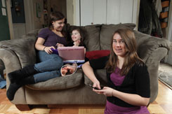 Heather Nokes, 18, watches as her 3-year-old sister Kaci, 3, uses a Barbi Learning Laptop for math and spelling practice, while Wendy, 13, holds her cellphone in their Winchester, Va., home. All born after 1990, the sisters are considered part of what sociologists are calling the iGeneration.