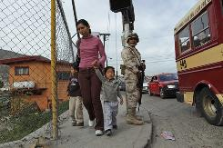 A woman walks with children near a military checkpoint in Tijuana, Mexico, last month. The government stepped up its fight against drug cartels, sending hundreds of soldiers to the border city, where violence has risen.
