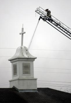 A firefighter shoots water at the steeple of Russell Memorial United Methodist Church in Wills Point, Texas, on Feb. 4.