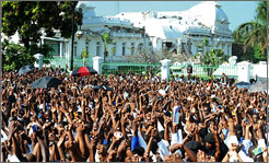 Thousands of Haitians join hands during an outdoor Mass in front of the destroyed presidential palace in downtown Port-au-Prince on Friday.