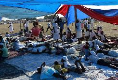 People lie under plastic tarps at a makeshift church inside a refugee camp in the Cite Soleil neighborhood in Port-au-Prince on Friday.