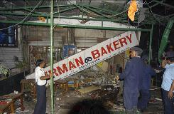 Indian police and rescue workers inspect the scene of an explosion in a German Bakery business close to the Osho Ashram in Pune, India, Saturday. A powerful explosion rocked the bakery in the western Indian city of Pune on Saturday.